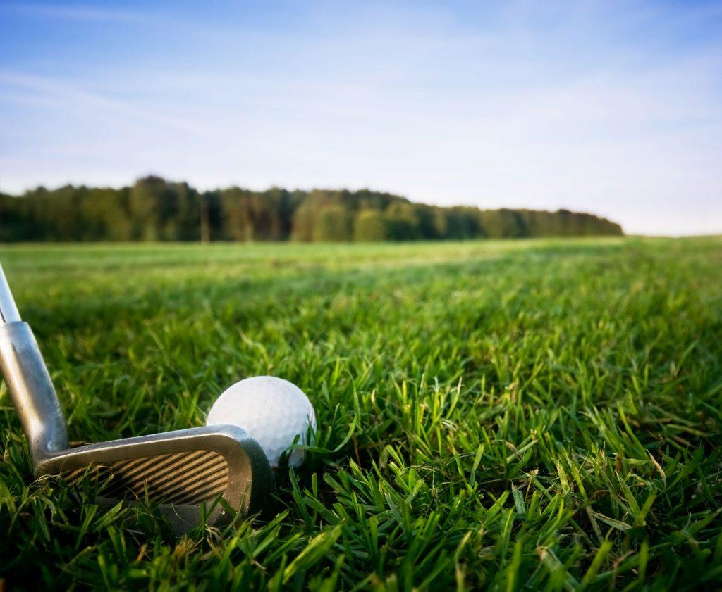 Un gros plan d'un fer prêt à frapper une balle de golf au milieu d'un champ